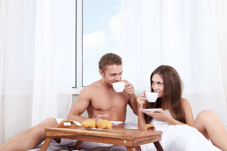 Young couple at breakfast in bed in the bedroom photo