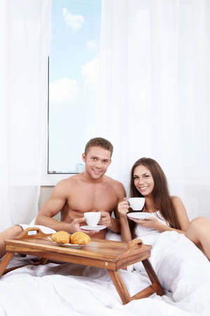 Young couple at breakfast in the bedroom photo