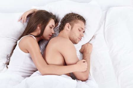 Young couple embracing in bed asleep photo