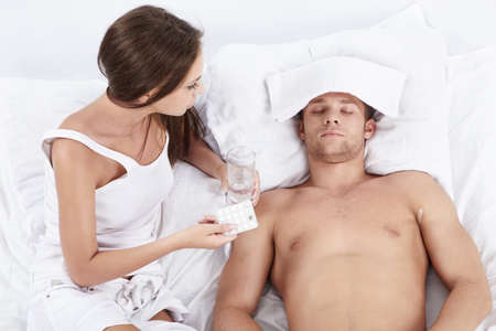 An attractive young woman holding tablet and the water in front of male patients in bed photo