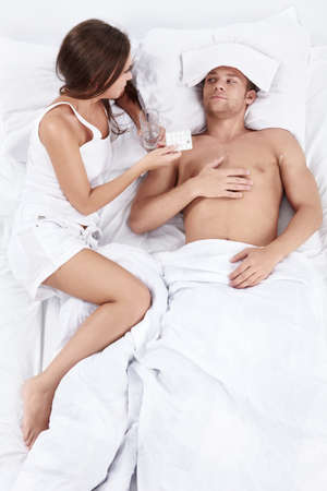Attractive girl gives tablets sick man in bed photo