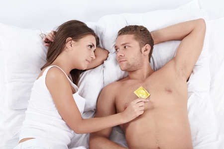Young attractive couple in bed with a condom photo