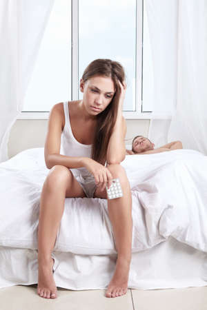 stressed man: Upset girl with pills next to a sleeping man