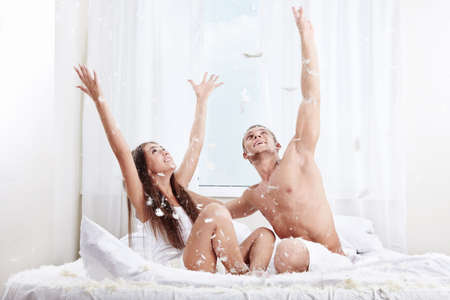 A smiling young couple caught feathers on the bed