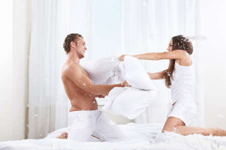 white pillow: Young couple fighting pillows on the bed