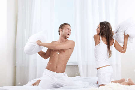 Pillow fight: Young couple fighting pillows in the bedroom