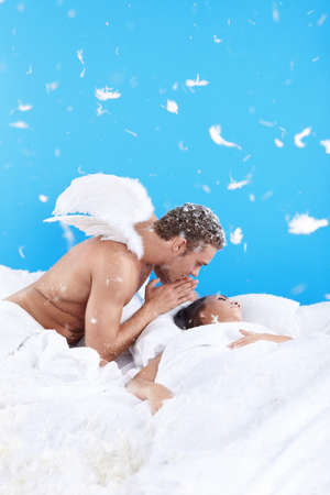 An attractive man with wings whispers sleeping girl photo
