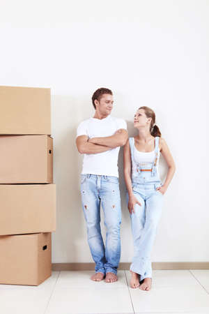 Young couple on a background of white walls with boxes photo