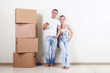 Young couple with boxes and flat keys photo
