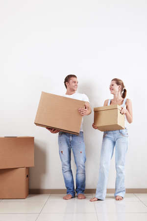 Attractive couple in the apartment carry boxes photo
