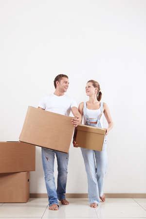 A young couple moves boxes in apartment photo