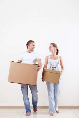 Attractive couple moves cardboard boxes in new home photo