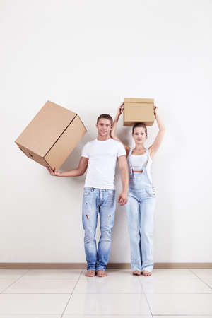 A young couple holds boxes in apartment photo