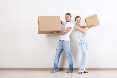 A smiling young couple with a cardboard box photo