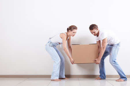 Young couple gently drags a box photo