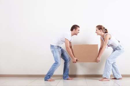Young smiling couple carries a box photo