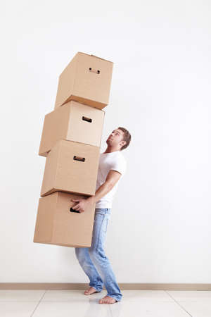 A young man holding four boxes photo