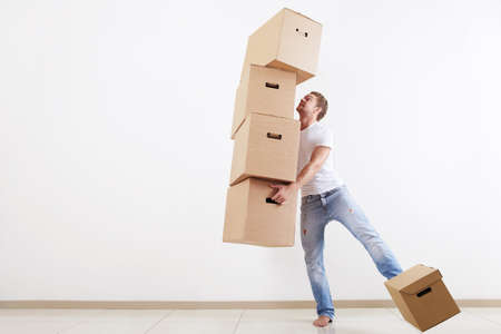 A young-looking man trying to carry all the boxes Stock Photo - 7944733