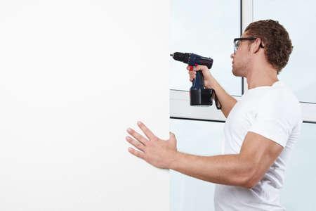 empleadas domesticas: Un hombre joven con gafas, trabajando con un taladro  Foto de archivo