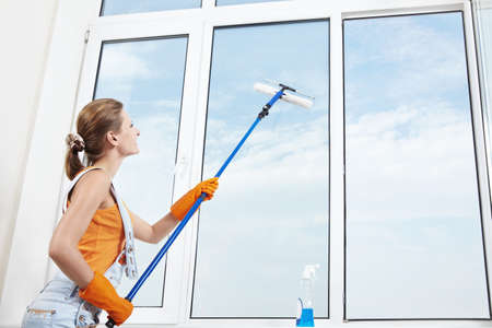 woman window: Attractive young girl washes windows