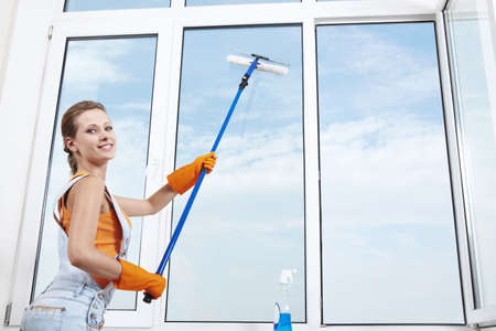 housewife gloves: Young attractive girl washes window