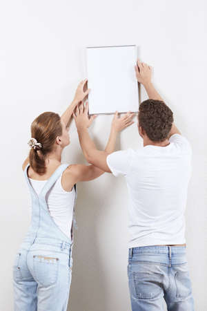 Young couple hanging up painting on the wall photo