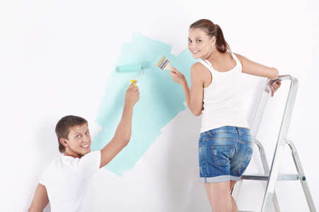 Young attractive couple paints the wall photo