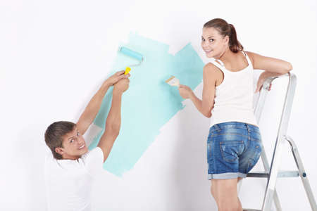 Attractive young couple paint the walls photo