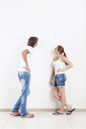 Young couple looking at hanging on the wall frame photo