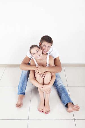 couple enlac�: Couple heureux embrassant sur le plancher  Banque d'images