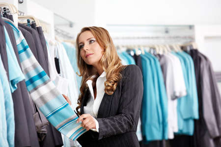 considers: The attractive girl considers clothes in shop  Stock Photo