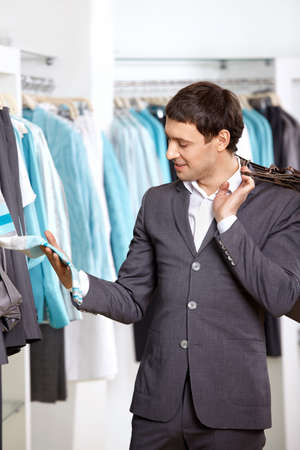 The young man considers clothes in shop photo