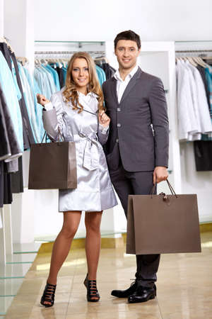 Smiling couple in shop of clothes with purchases  photo