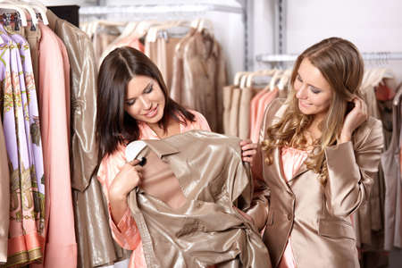 Two attractive girls try on clothes in shop photo