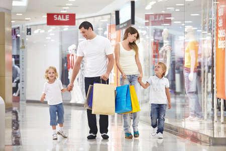 ni�os de compras: Joven familia con dos hijos caminando a las tiendas