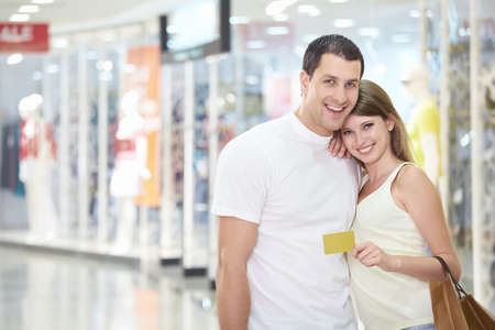 Beautiful couple in the store with credit card photo
