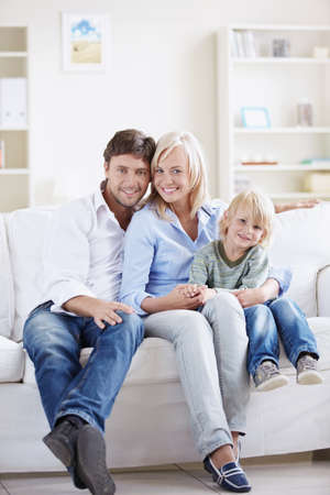 family on couch: Attractive young family with a child at home