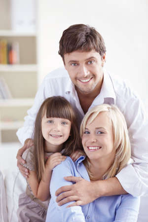 Embracing a young family facing the camera Stock Photo - 8096787