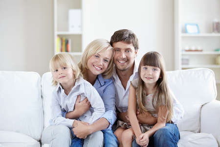 family on couch: Young families with children at home Stock Photo