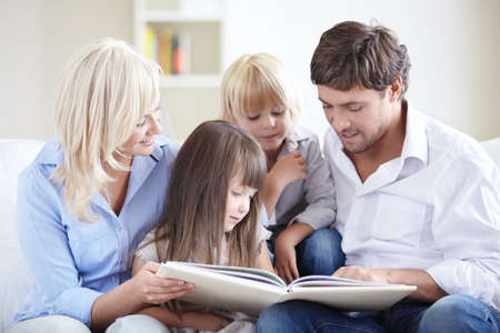 parent and child: Young parents reading a book for young children Stock Photo