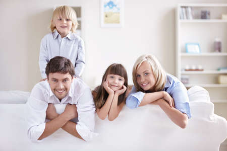 family on couch: Happy young family with children at home
