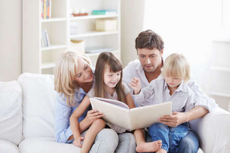 Young parents read the book to children at home Stock Photo - 8096729