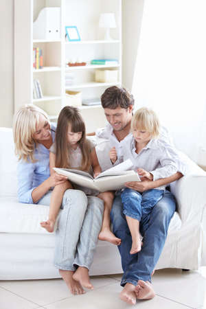Young parents read the book to children at home photo