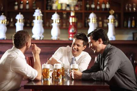 hombre tomando cerveza: Tres hombres en camisetas en la barra de