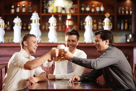 Three young men bob mugs in the bar