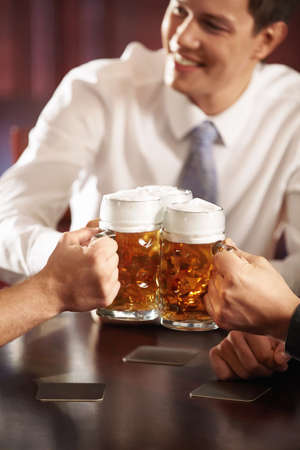 social drinking: Men with big mugs of beer close up