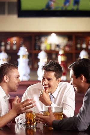 hombre tomando cerveza: Hombres hablan una cerveza en el bar