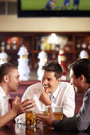 Men speak out for a beer at the bar photo