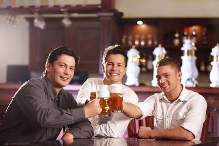 horizontal bar: Young business men in a bar with beer