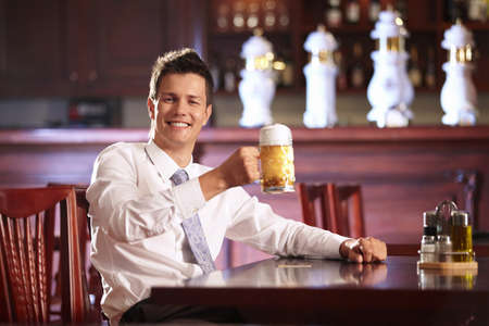 social drinking: Joyous young man holding a mug of beer Stock Photo
